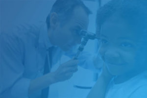 An ENT pediatrician looks into the ear of a child using an otoscope